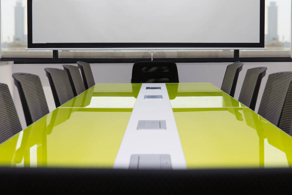 Green conference table with black chairs